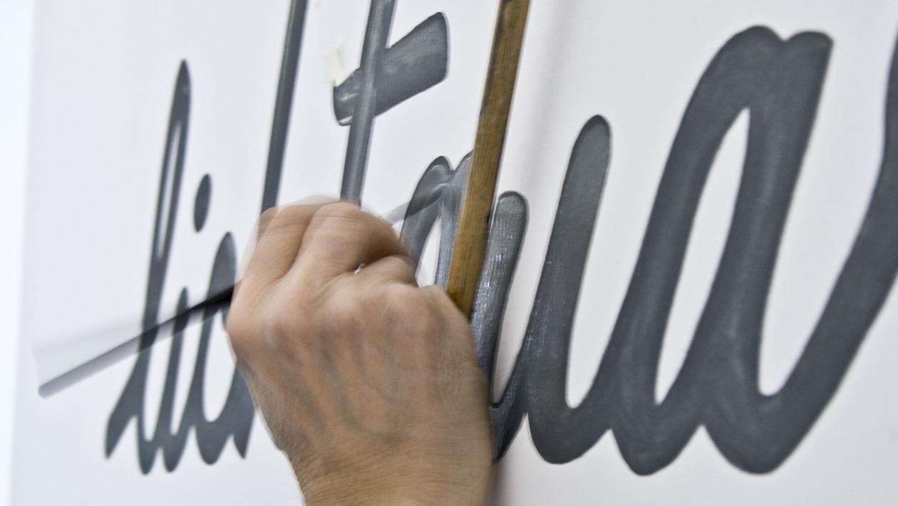 Detailfoto einer Hand beim Malen eines Logoschriftzugs